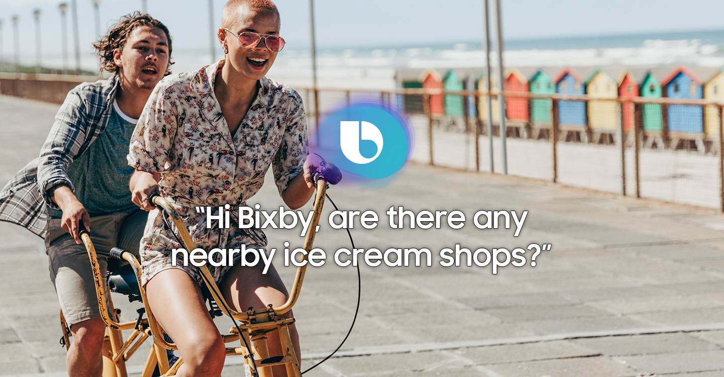 """An image of displaying the message """"Hi Bixby, are there any nearby ice cream shops?"""" on a picture of two people riding bicycles on the waterfront"""