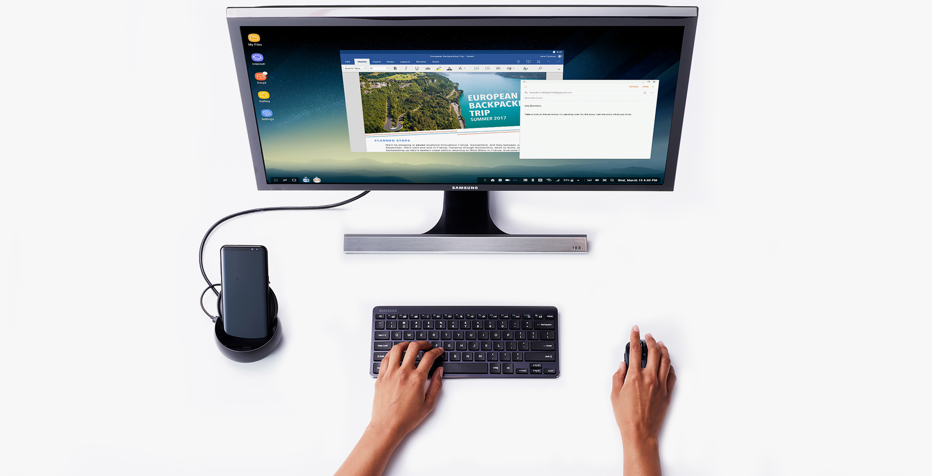 Image of using keyboard and mouse, in front of monitor and Galaxy S8 Black connected to Samsung DeX Station.