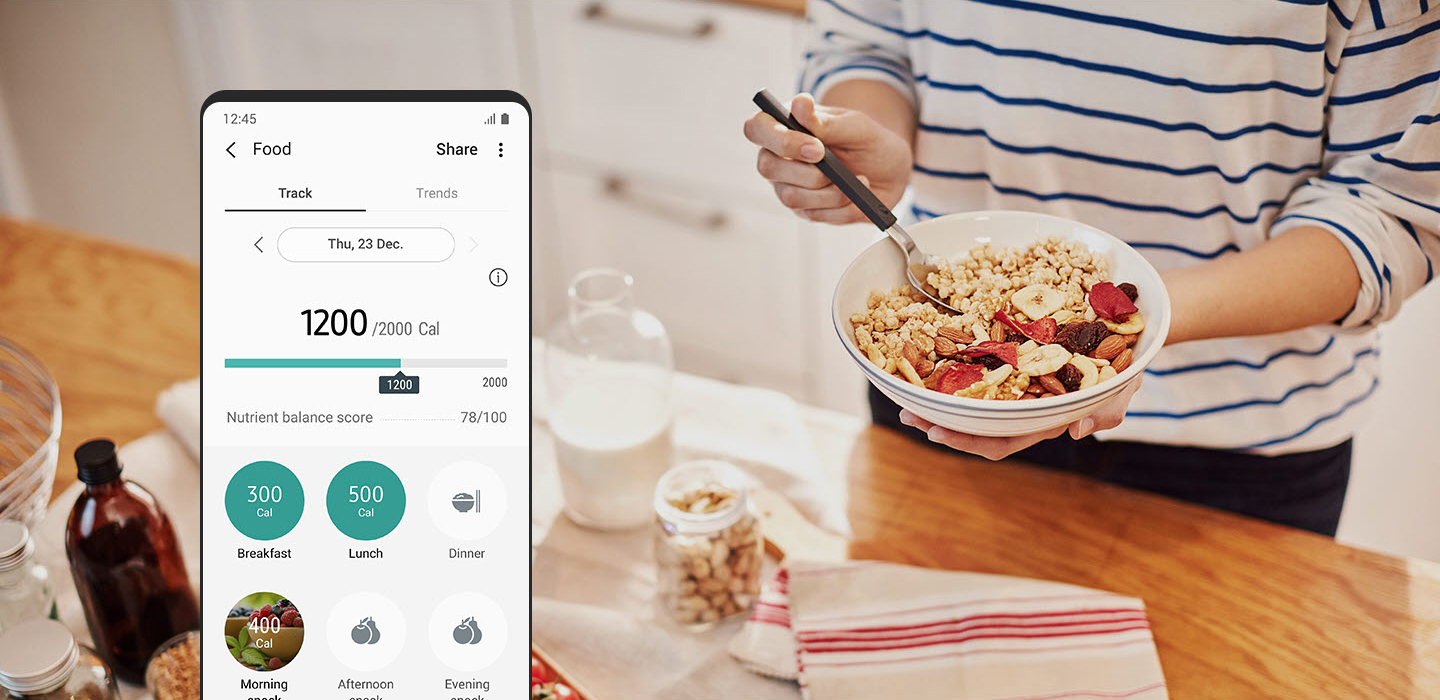 Someone is eating some cereal in the kitchen. A smartphone screen shows calorie content and nutritional balance score in the Samsung Health app.