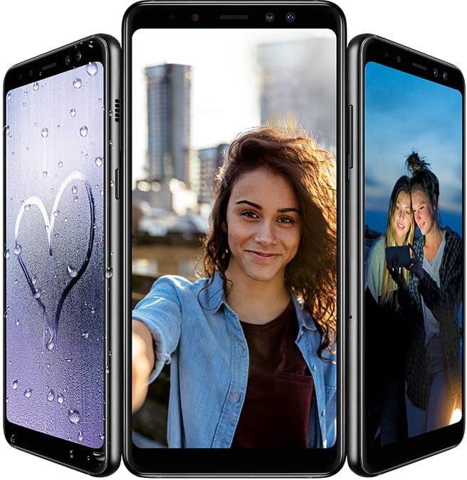 Three Galaxy A8 phones in black with onscreen photos representing functions: Galaxy A8 on the left displaying water resistance with a photo of a heart drawn in condensation, Galaxy A8+ in the middle displaying a Live focus selfie of a woman against a skyline, and Galaxy A8 on the right displaying the low light camera with a photo of two women taking a selfie at night.